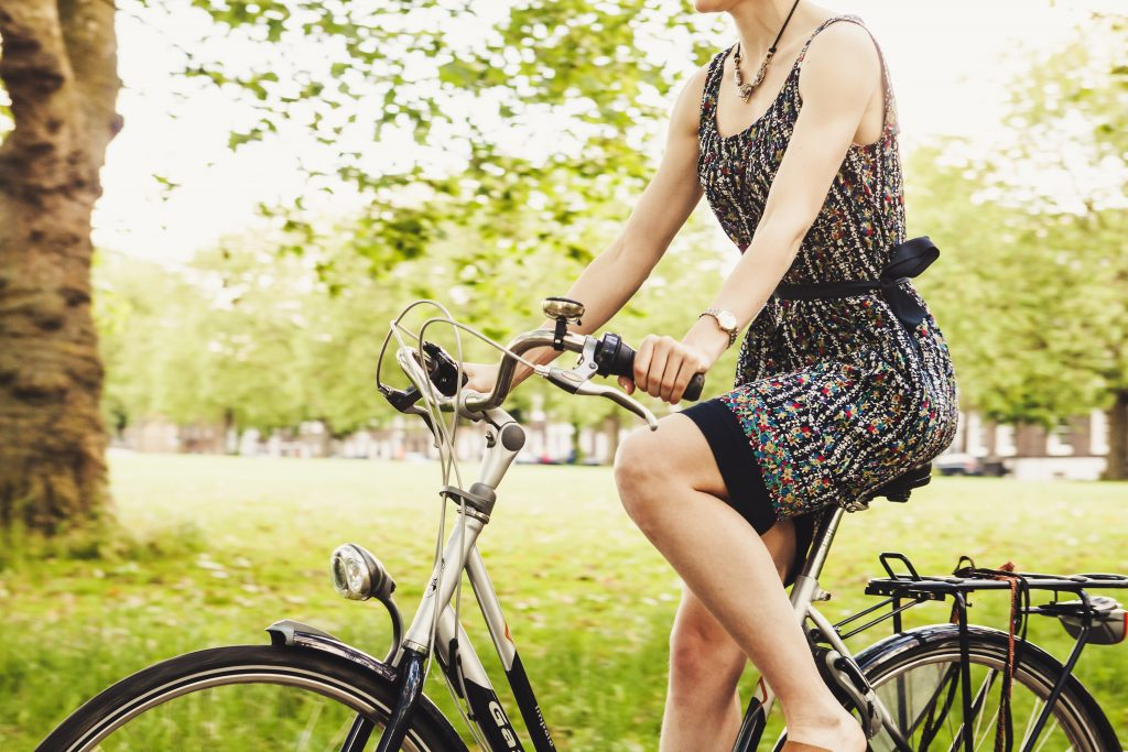 Healthy woman in a sundress riding a bicycle through a park