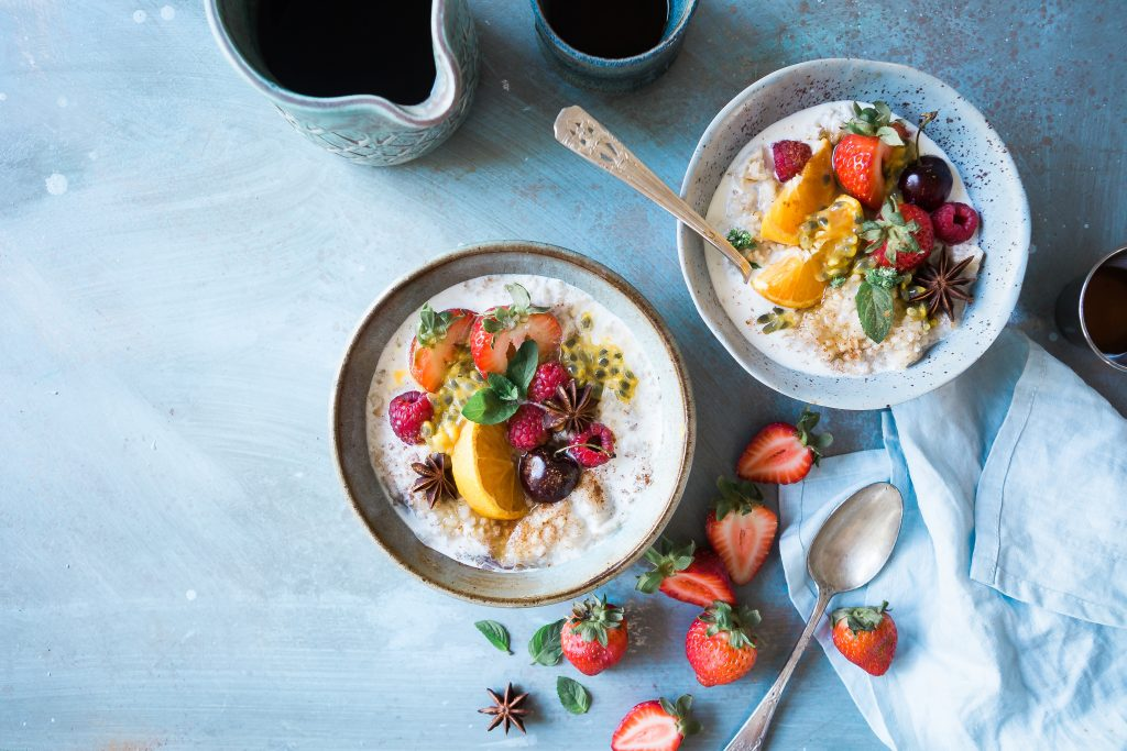 Two bowls of oatmeal and fruit