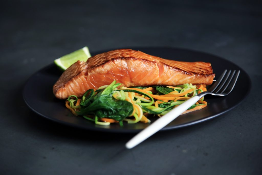 Beautiful plaate of grilled fish with lime on a bed of spinach, carrots and zucchini noodles