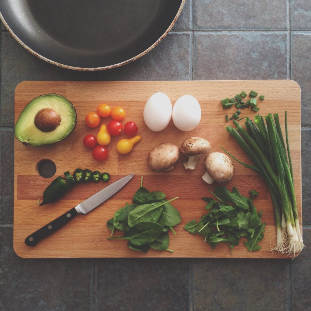Cutting board with lots of healthy vegetables and herbs