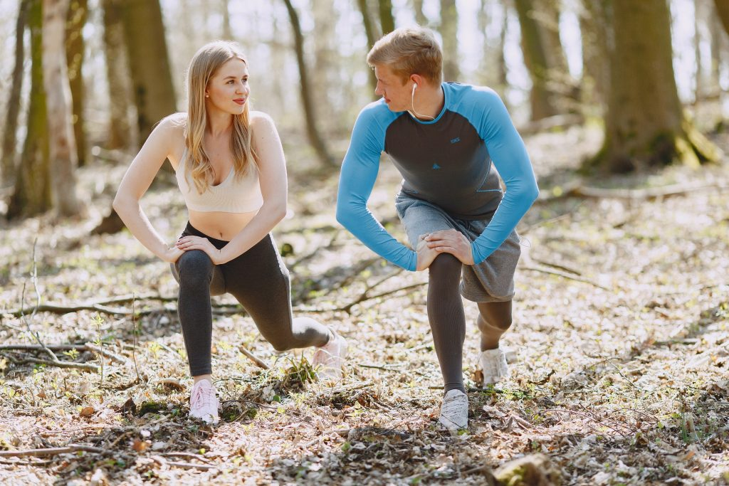 photo of youthful couple stretching with exercise